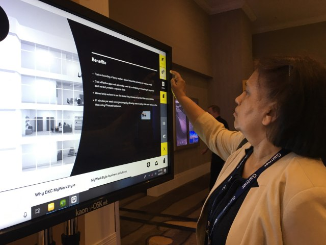 Woman uses multi-touch screen to explore a Kaon interactive application.